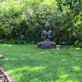 Buddha Fluss Stein sitzend Garten