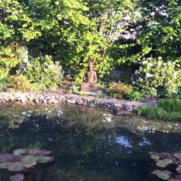 Buddhafigur sitzend am Teich