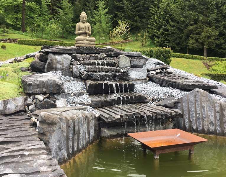 Stein Buddha am Wasserfall