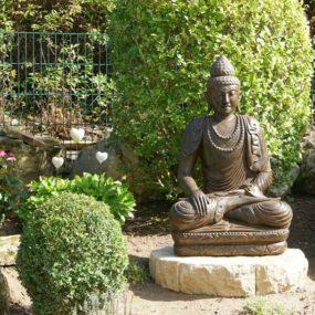Buddha Figur mit Mala im Garten